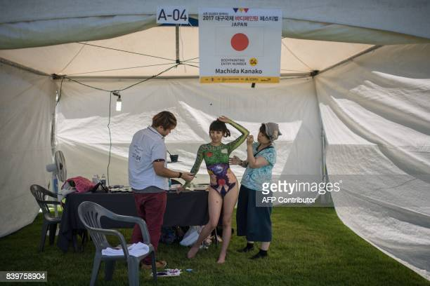 In this photo taken on August 26 contestant Machida Kanako of Japan applies her designs to a model during the Daegu International Bodypainting...