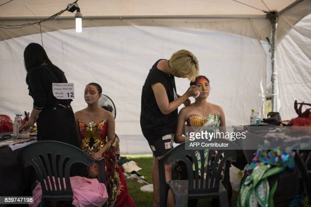 In this photo taken on August 26 contestants from South Korea apply designs to their models during the Daegu International Bodypainting Festival in...