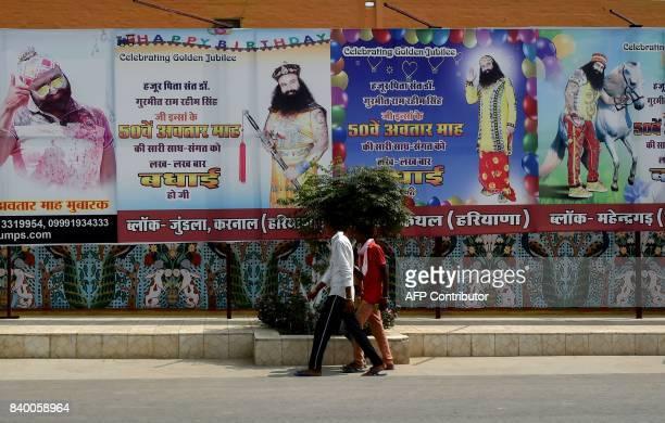 In this photo taken on August 27 2017 followers of the controversial Indian guru Ram Rahim Singh walk outside the 'Dera Sacha Sauda' ashram in Sirsa...