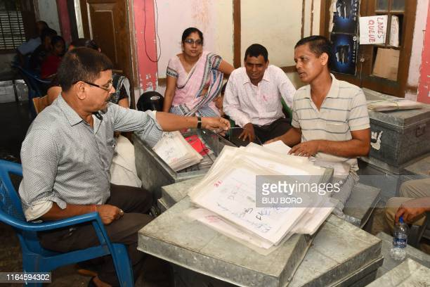 In this photo taken on August 28 workers at the National Register of Citizens office check documents submitted by people for the NRC ahead of the...
