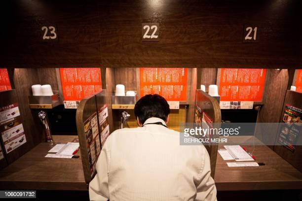 In this photo taken on August 29 a customer sitting in a partitioned booth eats his ramen noodles at a chain restaurant in Tokyo Analysts say that...