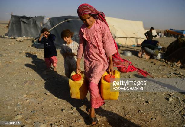 In this photo taken on August 3 a droughtdisplaced Afghan girl carries water containers filled from a tanker at a camp for internally displaced...