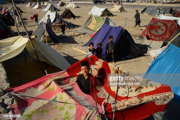 In this photo taken on August 3 droughtdisplaced Afghan children look on from their tents at a camp for internally displaced people in Injil district...