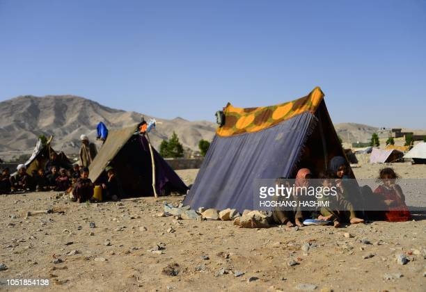 In this photo taken on August 3 droughtdisplaced Afghan children look on from their tent at a camp for internally displaced people in Injil district...