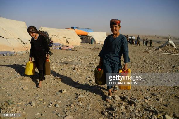 In this photo taken on August 3 droughtdisplaced Afghan children carry water containers filled from a tanker at a camp for internally displaced...