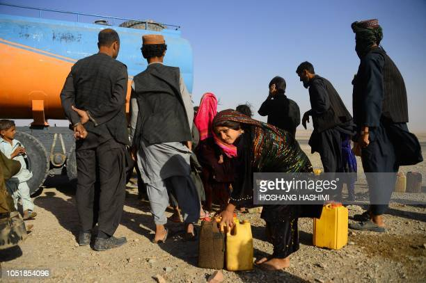 In this photo taken on August 3 droughtdisplaced Afghan people fill water containers from a tanker at a camp for internally displaced people in Injil...