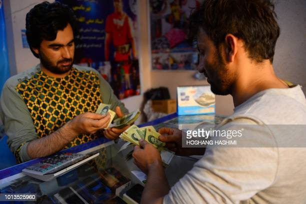In this photo taken on August 4 an Afghan returnee from Iran counts Iranian rial banknotes at a currency exchange in the Afghan province of Herat...