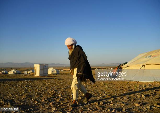 In this photo taken on August 5 a droughtdisplaced Afghan man walks outside his tent at a camp for internally displaced people in Injil district of...