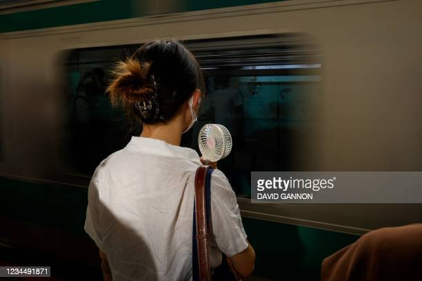 In this photo taken on August 5 a woman uses a hand-held fan to stay cool as a commuter train arrives in Tokyo's Shinjuku Station as Japan's capital...