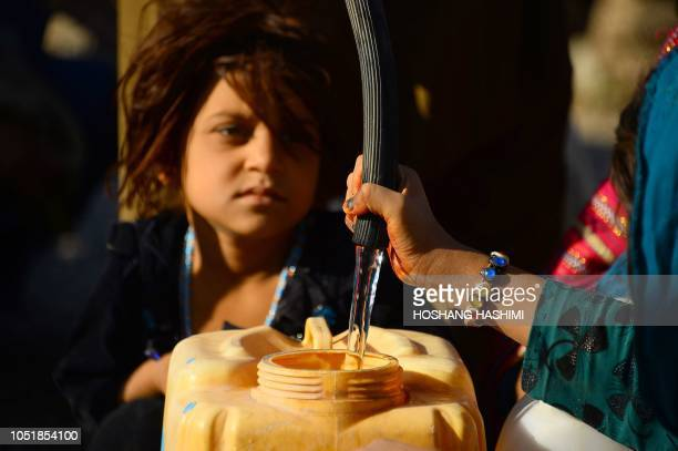 In this photo taken on August 5 droughtdisplaced Afghan children fill water containers from a tanker at a camp for internally displaced people in...