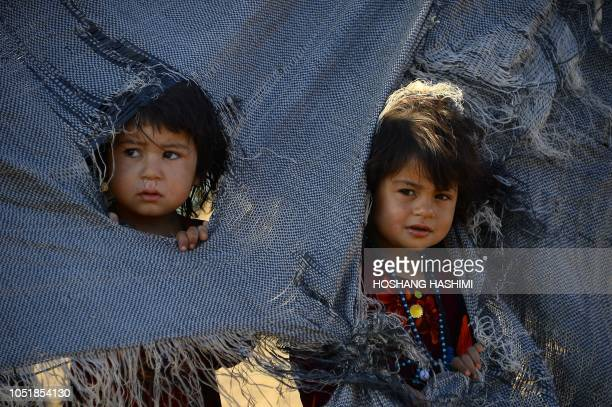 TOPSHOT In this photo taken on August 5 droughtdisplaced Afghan children look on from their tent at a camp for internally displaced people in Injil...