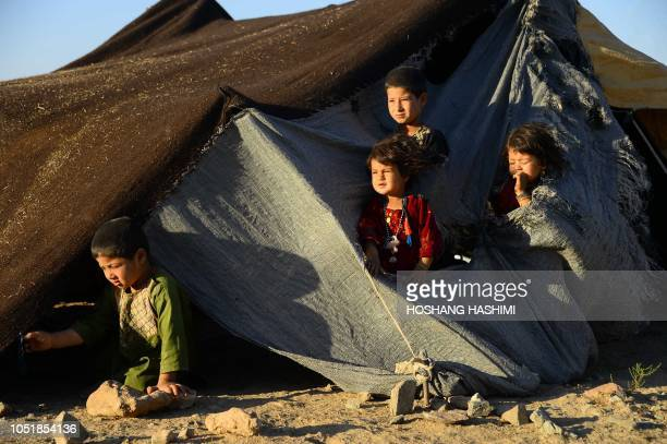 In this photo taken on August 5 droughtdisplaced Afghan children look on from their tent at a camp for internally displaced people in Injil district...