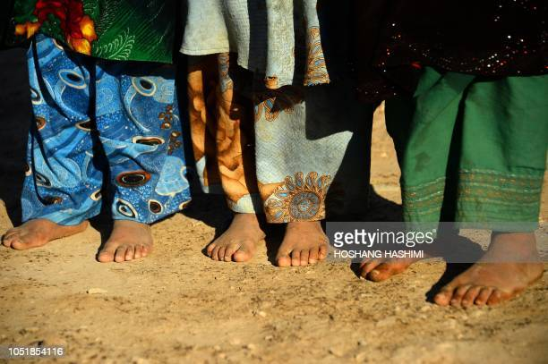 In this photo taken on August 5 droughtdisplaced Afghan children stand barefoot outside of their tent at a camp for internally displaced people in...