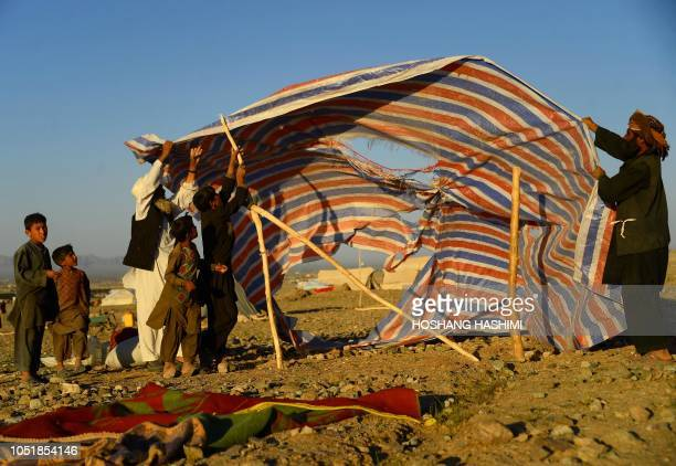 In this photo taken on August 5 droughtdisplaced Afghan people erect a tent at a camp for internally displaced people in Injil district of Herat...