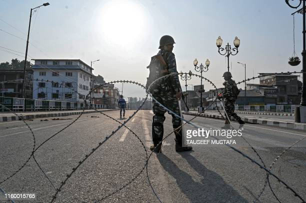 TOPSHOT In this photo taken on August 5 Indian paramilitary troopers stand guard behind a barbed fence wire as they block a road during a curfew in...