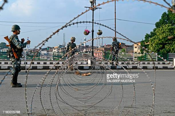 In this photo taken on August 5 Indian paramilitary troopers stand guard near a barbed fence wire as they block a road during a curfew in Srinagar...