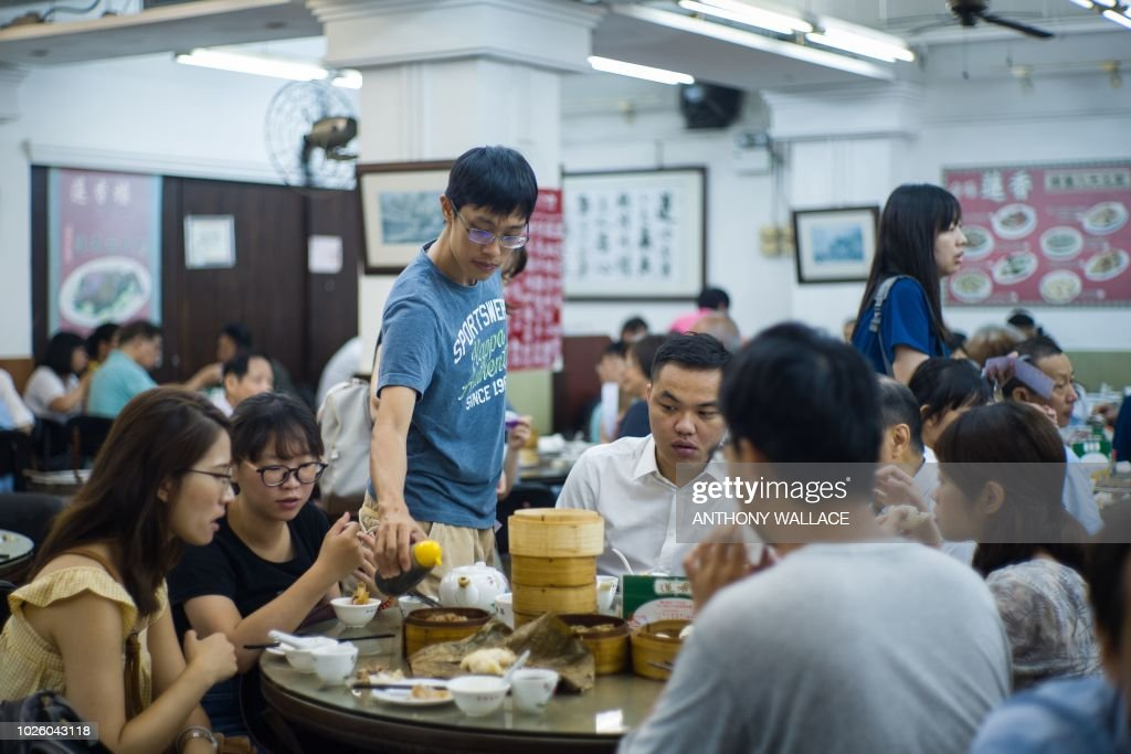 In this photo taken on August 7, 2018, a man pours soy sauce onto a dim sum dish at the Lin Heung Tea House in Hong Kong. - Lin Heung Tea House, one of Hong Kong's most famous restaurants, says the the new owner of the building which houses the restaurant has not yet contacted them about renewing their lease, despite it expiring early next year, and they feel in the dark about the landlord's intentions. That has sparked fears that Lin Heung will be the latest Hong Kong culinary treasure to fall foul of the city's thirst for redevelopment. (Photo by Anthony WALLACE / AFP) / TO GO WITH HongKong-food-drink-culture-lifestyle-dimsum, FEATURE by Jasmine LEUNG