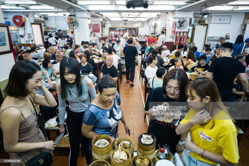 In this photo taken on August 7, 2018, diners stand around a trolley of bamboo steamers containing freshly steamed dim sum dishes at the Lin Heung Tea House in Hong Kong. - Lin Heung Tea House, one of Hong Kong's most famous restaurants, says the the new owner of the building which houses the restaurant has not yet contacted them about renewing their lease, despite it expiring early next year, and they feel in the dark about the landlord's intentions. That has sparked fears that Lin Heung will be the latest Hong Kong culinary treasure to fall foul of the city's thirst for redevelopment. (Photo by Anthony WALLACE / AFP) / TO GO WITH HongKong-food-drink-culture-lifestyle-dimsum, FEATURE by Jasmine LEUNG
