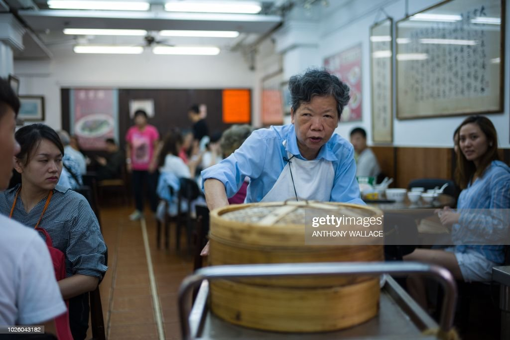 In this photo taken on August 7, 2018, diners watch as a trolley lady as she passes them with bamboo steamers containing dim sum dishes at the Lin Heung Tea House in Hong Kong. - Lin Heung Tea House, one of Hong Kong's most famous restaurants, says the the new owner of the building which houses the restaurant has not yet contacted them about renewing their lease, despite it expiring early next year, and they feel in the dark about the landlord's intentions. That has sparked fears that Lin Heung will be the latest Hong Kong culinary treasure to fall foul of the city's thirst for redevelopment. (Photo by Anthony WALLACE / AFP) / TO GO WITH HongKong-food-drink-culture-lifestyle-dimsum, FEATURE by Jasmine LEUNG