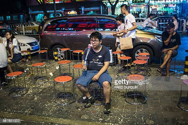 TOPSHOT In this photo Taken on August 9 a man smells a rose as he waits for a table at a restaurant during the Qixi Festival or Chinese Valentine's...