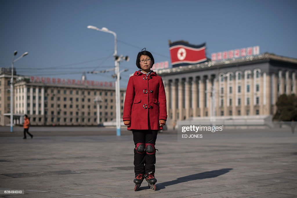 In this photo taken on December 1, 2016, student Kim Hong poses for a photo as she practices rollerblading on Kim Il-Sung square in Pyongyang. / AFP / Ed JONES / This photo package is accompanied by a blog piece written by staff photographer Ed Jones https://goo.gl/lEZ8Fk