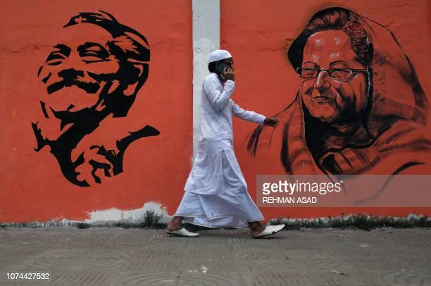 TOPSHOT In this photo taken on December 16 2018 a man walks past a wall with images of Bangladeshi founding father Sheikh Mujibur Rahman and Prime...