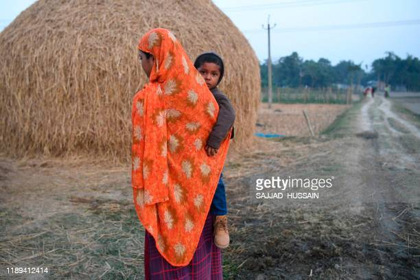 In this photo taken on December 16 a woman holds her child next to farming fields in Barpeta village in Assam HabiburRehman was locked up for four...