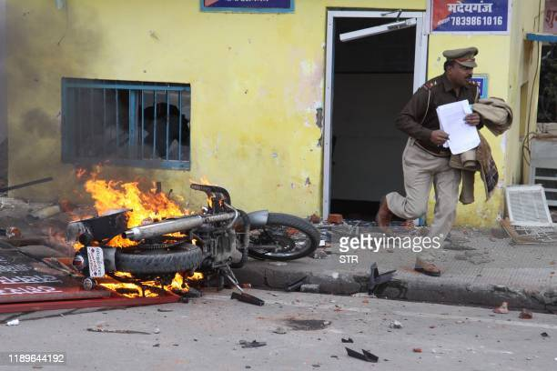 TOPSHOT In this photo taken on December 19 2019 an officer runs with documents from a police post damaged by protesters during a demonstration...