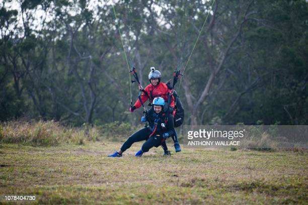 In this photo taken on December 21 university lecturer and youth counsellor Giovanni Lam and novice Yes Chan land after paragliding in tandem on Ma...