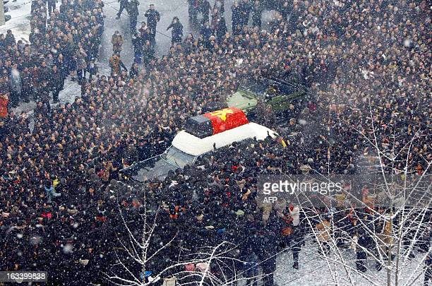 In this photo taken on December 28, 2011 a car is surrounded by mourners as it carries the casket containing Kim Jong-Il's body during the funeral...