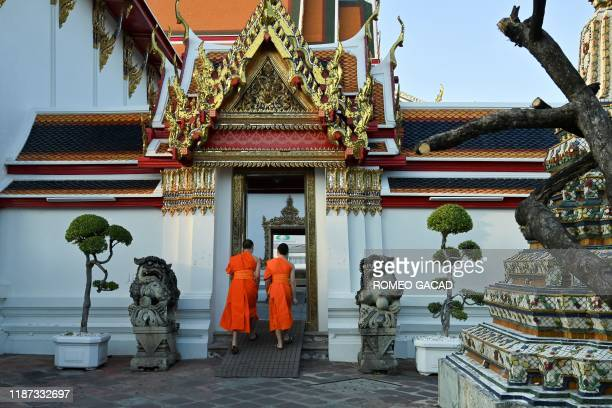 In this photo taken on December 3, 2019 Buddhist monks enter a temple at Wat Po temple complex in Bangkok. - Widely practiced across Thailand, from...