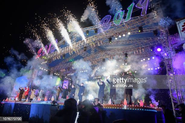 In this photo taken on December 31 performers stand on a stage during a New Year's eve countdown event and fireworks display on Kim Il Sung Square in...