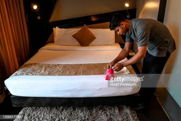 In this photo taken on February 10, 2020 a staff member arranges a packet of 'love kit' as he prepares a room at the Dragonfly hotel in Mumbai. -...