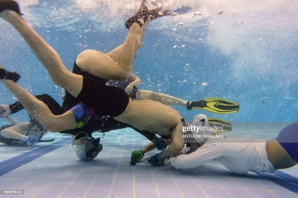 TOPSHOT - In this photo taken on February 15, 2017, members of the 'HK Typhoon' underwater hockey club fight for possession of the puck during their once-a-week team practise session at a 25-metre school pool in Hong Kong. The gravity defying sport of underwater hockey has gained a worldwide following -- now a Hong Kong team is diving in as the game takes off in Asia. / AFP PHOTO / Anthony WALLACE / TO GO WITH HongKong-sport-lifestyle-underwater-hockey,FEATURE by Aaron TAM