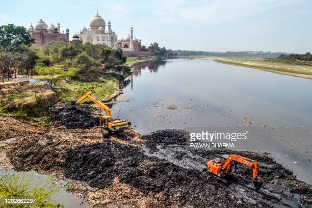 In this photo taken on February 19 Agra Municipal Corporation workers use excavators to clean the banks of the Yamuna river behind the Taj Mahal in...