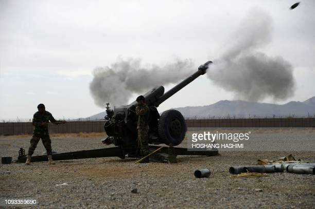 In this photo taken on February 2 an Afghan National Army soldier fire a D30 122mm Howitzer gun as members of the NATO military forces look on during...