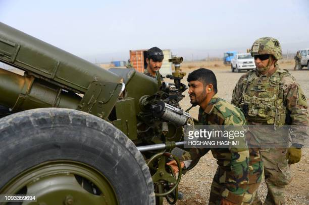 In this photo taken on February 2 an Afghan National Army soldier prepares to fire a D30 122mm Howitzer gun while a member of the NATO military...