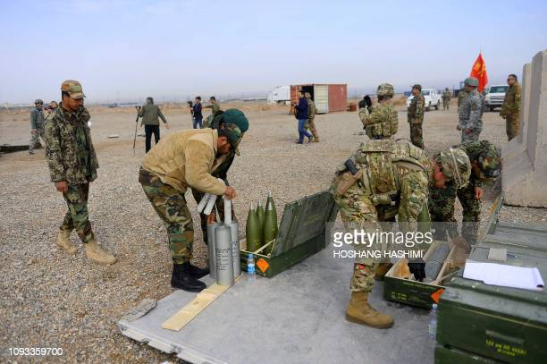 In this photo taken on February 2 US military personnel and Italian NATO forces soldiers along with Afghan National Army prepare shells during a...