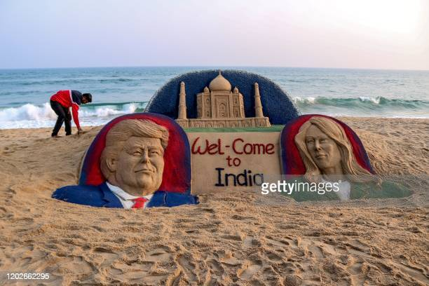 In this photo taken on February 22 artist Sudarsan Pattnaik bends near his sand sculpture representing US President Donald Trump and his wife Melania...