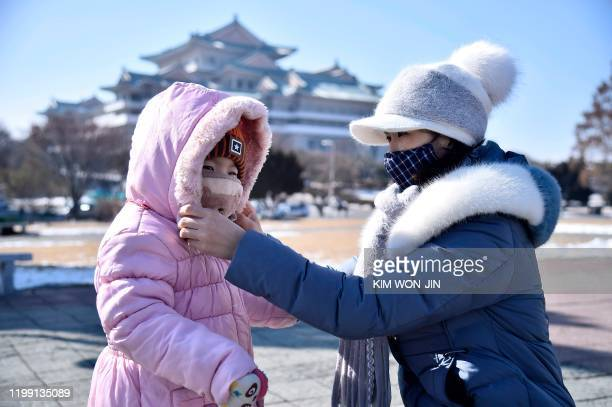 In this photo taken on February 6 a woman helps her daughter seen wearing a face mask in Pyongyang At least 31000 people have been infected and more...