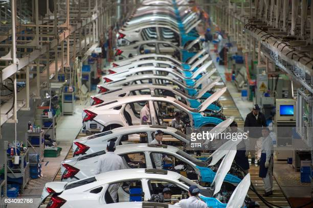 In this photo taken on February 6 employees work on the Honda Civic production line at the automaker's Dongfeng Honda factory in Wuhan, China's Hubei...