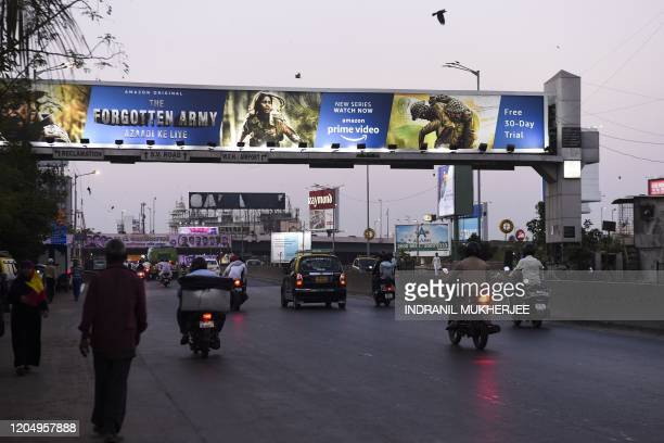 In this photo taken on February 7 commuters drive along a road past a billboard in Mumbai advertising the Amazon Prime Video online series The...