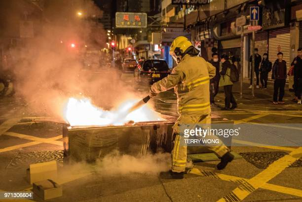 In this photo taken on February 9 a firefighter extinguishes a burning object during clashes bewteen protesters and the police later dubbed the...