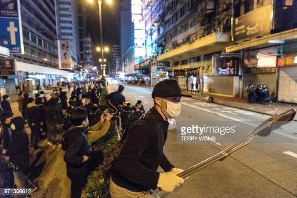 In this photo taken on February 9 a protestor holds a folding chair as he and others gather during clashes with police later dubbed the Fishball...