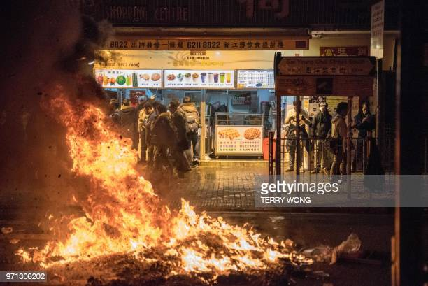 TOPSHOT In this photo taken on February 9 customers visit an eatery as a fire started by protesters burns in the street during clashes between...
