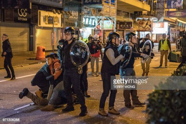 In this photo taken on February 9 police stand guard during clashes with protesters later dubbed the Fishball Revolution in the Mongkok area of Hong...