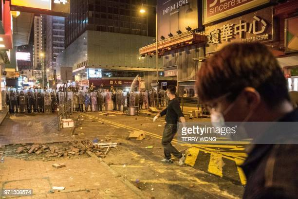 In this photo taken on February 9 protesters throw objects at police during clashes later dubbed the Fishball Revolution in the Mongkok area of Hong...