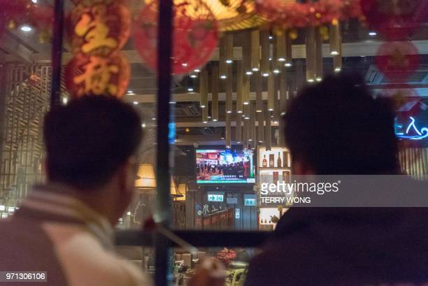 In this photo taken on February 9 two men watch live coverage of clashes between protesters and police later dubbed the Fishball Revolution in the...