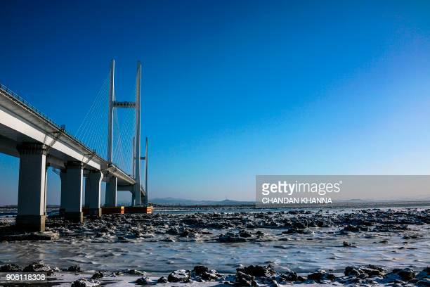 In this photo taken on January 11 a fourlane 350 million USD bridge with a new customs zone is seen over the Yalu river between the North Korean town...