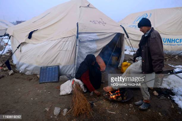 In this photo taken on January 14 Internally-displaced people warm up around a fire in front of their tent at a refugee camp on the outskirts of...